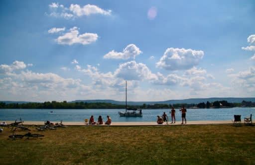 People relaxing by the grass with the lake and mountains in the background.