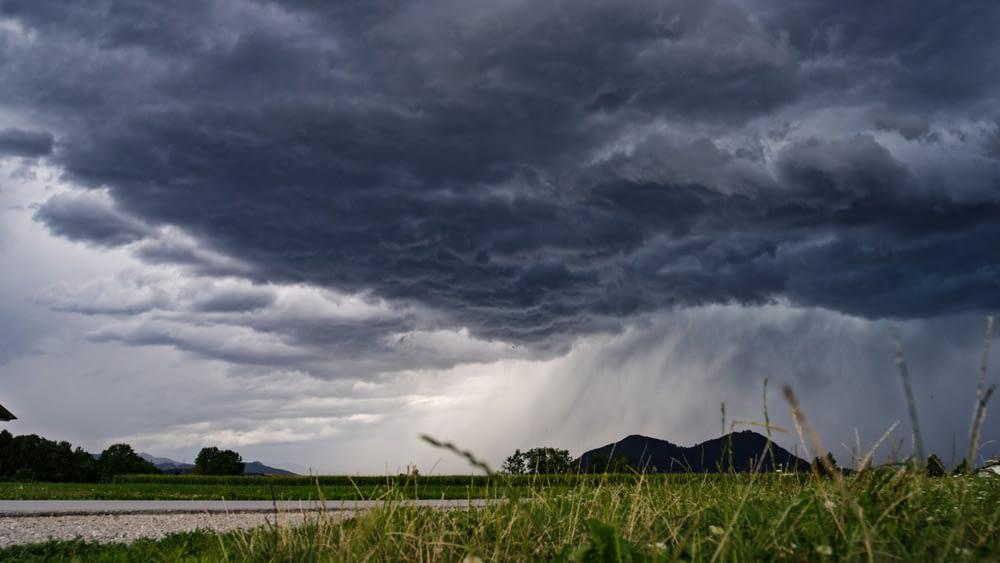 A prairie field with dark clouds above it