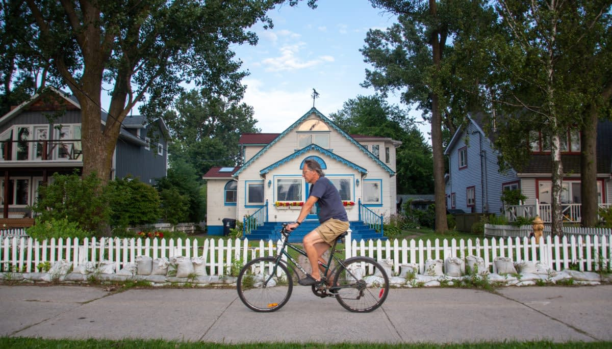 Man biking in front of cottage