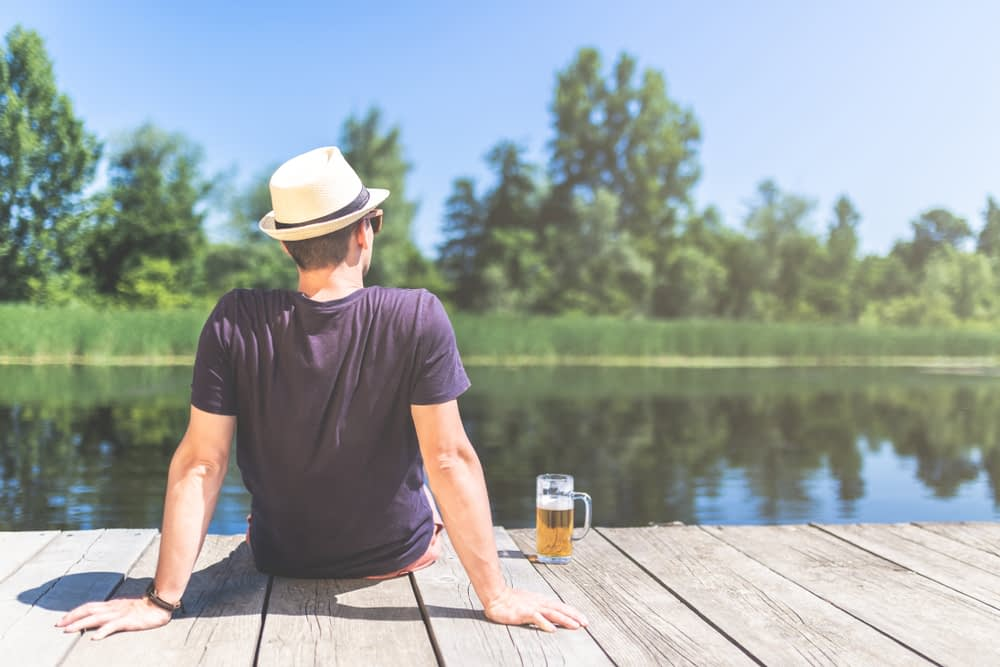 Man sitting on dock with beer